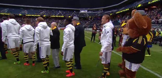 Les personnes âgées remplacent les enfants pour l'entrée des joueurs lors d'un match de football
